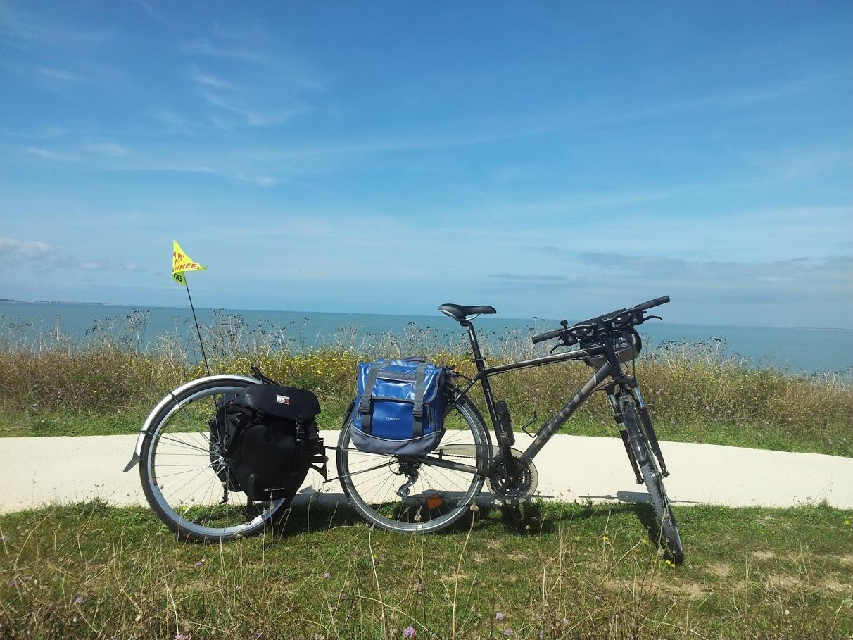 Vélo VTC aménagé pour le voyage avec roue-remorque de marque Extra Wheel, sacoches arrère et guidon (pas encore de sacoches avant) près du pont de l'Île de Ré (à proximité de La Rochelle) sur une piste cycblable croisant la Vélodyssée (EV1) sur le littoral atlantique
