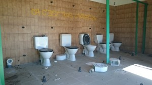 """Autre vue d'un bloc sanitaire. Les parois ont été """"récupérées"""" et le mur décoré visiblement par un fan de l'affaire """"Omar m'a tuer""""..."""