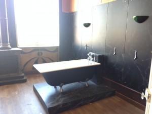 """La pièce """"Belle-époque"""" avec baignoire à l'ancienne et murs de marbre noir"""
