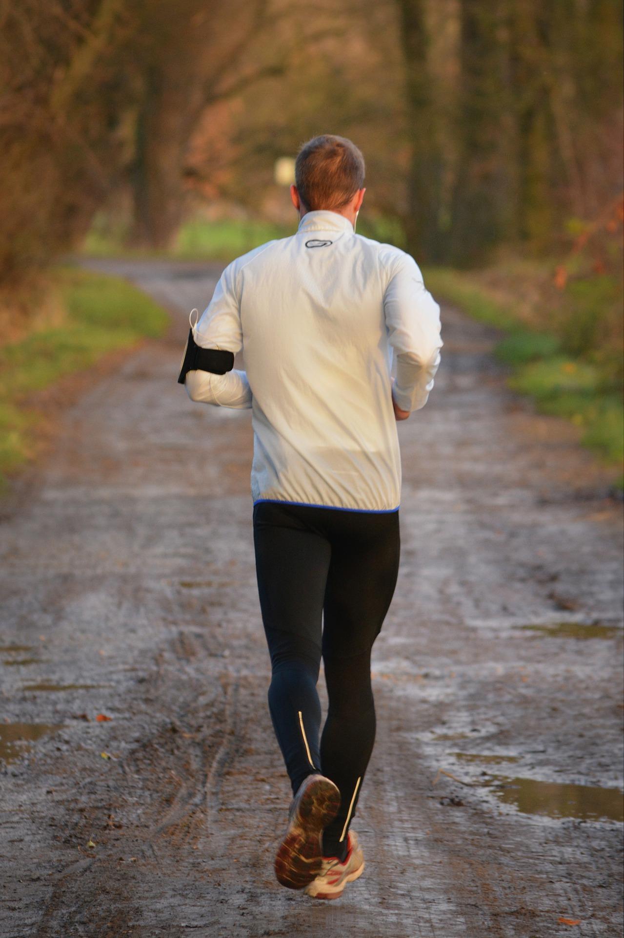 Un coureur amateur en pleine Nature avec sa ceinture cardio et son application sur smartphone