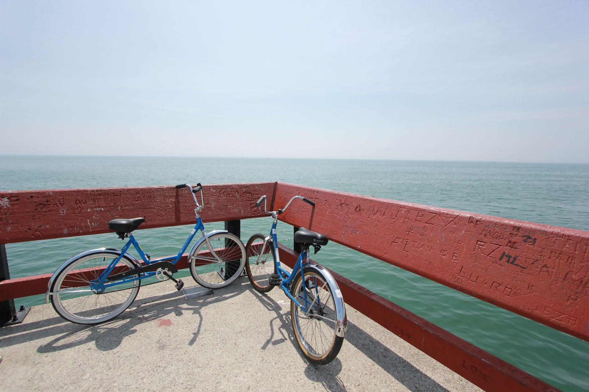 La gestion de l'autonomie du smartphone est indispensable pour garer ses deux vélos bleus contre une rambarde au bord de la mer !