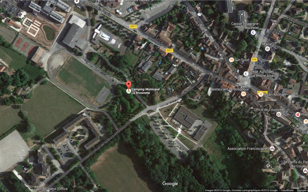 """Vue aérienne du centre de Morestel avec le camping municipal """"La Rivoirette"""" bordé du stade, des immeubles et d'une rue assez fréquentée. Peu enthousiasmant mais très pratique pour une pause lors d'une rando à vélo... et à un tarif défiant toute concurrence ! (capture d'écran de Google Maps)."""